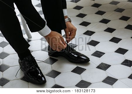 Close up male hands tying laces on black shiny shoes before wedding