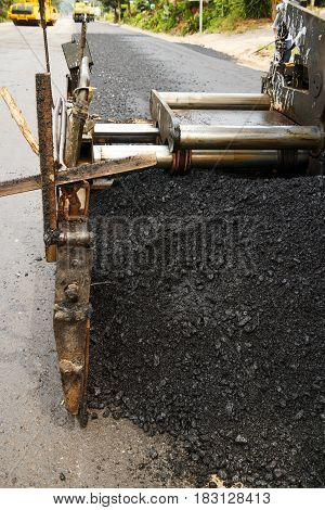 Close up asphalt spreader in work on site.