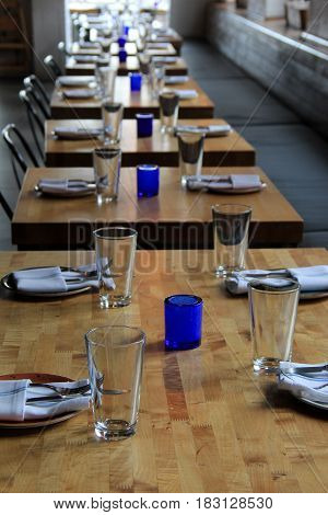Several tables placed together with settings ready for patrons to enter the restaurant for dinner.