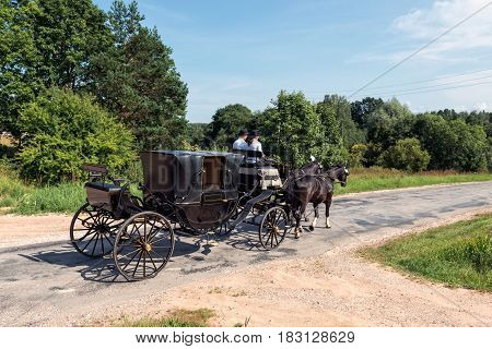 By the way leaves wedding carriage with two horses.