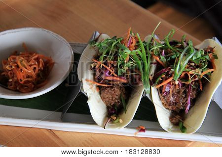 Tempting array of pulled pork tacos and side of flavored cabbage on tray in restaurant.
