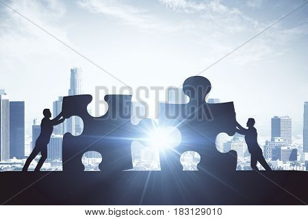 People silhouettes putting puzzle pieces together on city background with sunlight. Teamwork concept