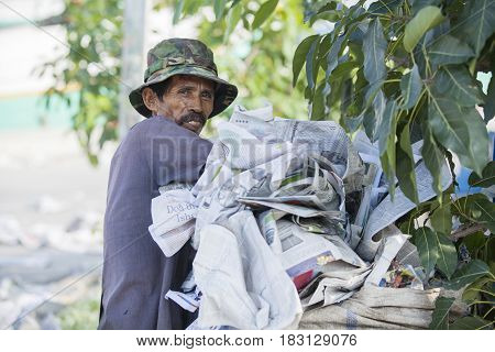 JAKARTA Indonesia. April 20 2017: old dustman looking at the camera while putting garbage of papers in the garbage bag