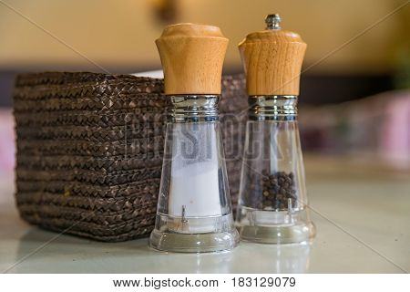 Closeup of salt and pepper glass bottles on wooden table in restaurant