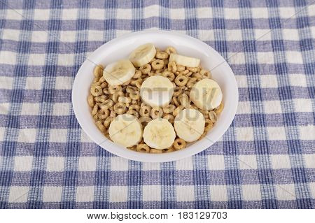 A white bowl of toasted oat cereal with sliced bananas on a blue plaid tablecloth