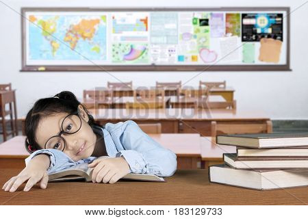 Portrait of exhausted schoolgirl looking at the camera while sleeping above a book