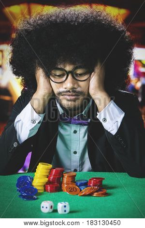 Afro man with curly hair sitting in the casino and looks frustrated after lose in gambling