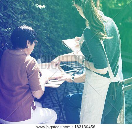 Waitress taking order from senior adult couple