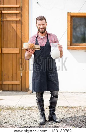 Full body portrait of a handsome farmer in apron standing with goat cheeses and milk outdoors on the rural house background