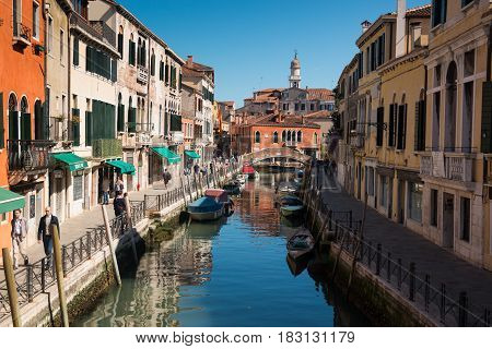 VENICE, ITALY - 09.04.2017: Narrow street with a canal bridge boats and tourists in Venice Italy