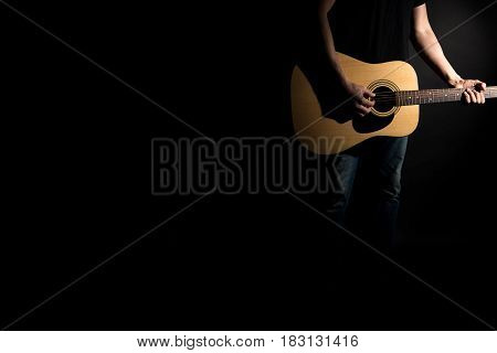 The Guitarist In Jeans Plays An Acoustic Guitar, On The Right Side Of The Frame, On A Black Backgrou