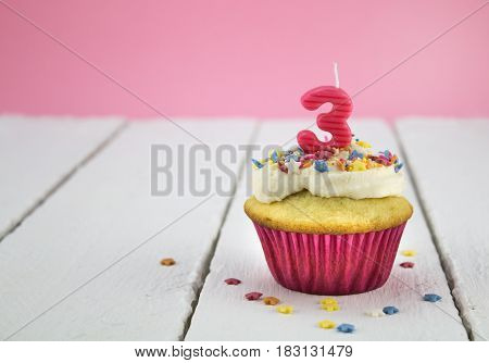Happy birthday cup cake with star sprinkles and number 3 pink candle on white tabel with pink background - Birthday celebration background for a little girl