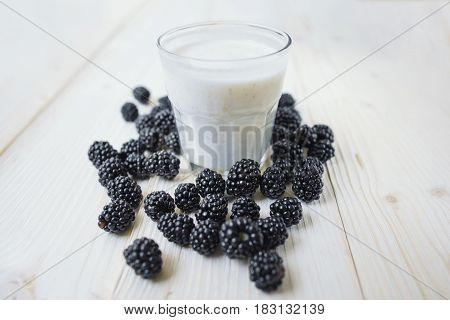 Rustic healthy breakfast with dewberry and yogurt in a glass on a wooden table. Glass of homemade yogurt with ripe berries. Healthy breakfast with vital vitamins.