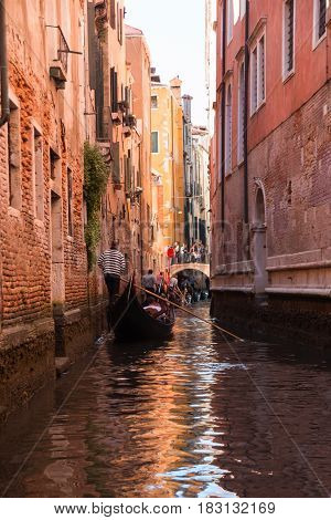 VENICE, ITALY - 09.04.2017: Gondola in narrow street with a canal bridge and tourists in Venice Italy
