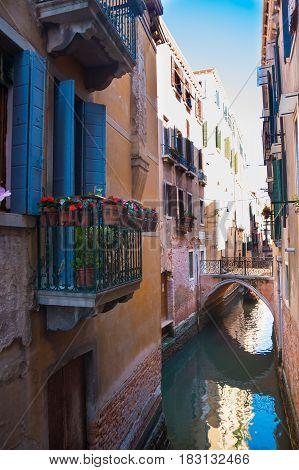 VENICE, ITALY - 09.04.2017: Narrow street with a canal bridge and balcony in Venice Italy