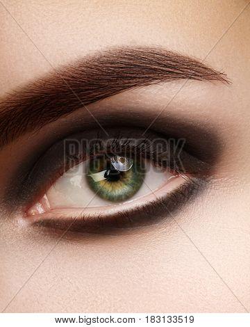 Beautiful macro photo of woman eye with black smoky makeup. Perfect shape eyebrows. Cosmetics and make-up. Close-up macro shot of fashion eyes visage