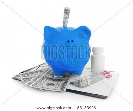 Ceramic piggy bank with dollar banknotes and pills on white background