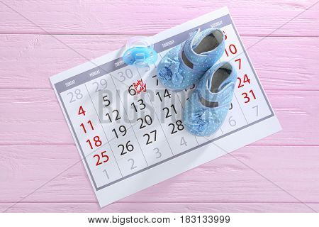 Calendar with baby booties on wooden background
