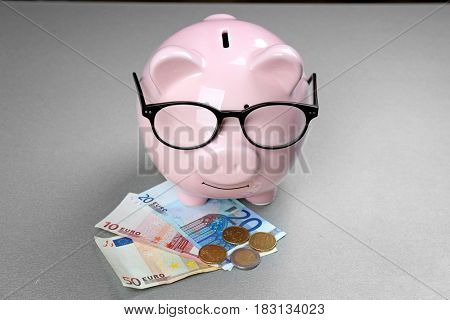 Saving electric power concept. Ceramic piggy bank with money on grey background