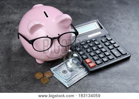 Saving electric power concept. Ceramic piggy bank with calculator and money on grunge background