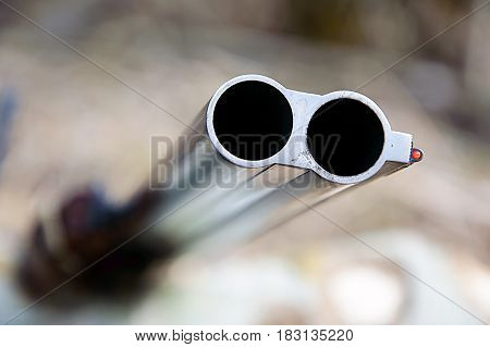 Muzzle of double barreled shotguns pointed - macro shooting. Hunting rifle takes aim at the victim. Eyes on the target.