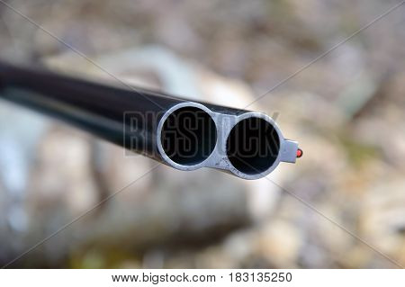 Muzzle of double barreled shotguns. Shotgun pointed at me - macro shooting. Hunting rifle takes aim at the victim. Eyes on the target.