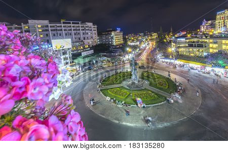 Dalat, Vietnam - March 28th, 2017: Roundabout intersections with lights Dalat night market, creating in streaks of color motorcycle stayed in the city for the evening mist Da Lat, Vietnam