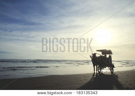 Yogyakarta Indonesia. April 20 2017: Silhouette of horse carriage with two children on the beach at sunset time