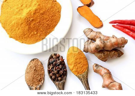 Turmeric roots with turmeric powder on white background
