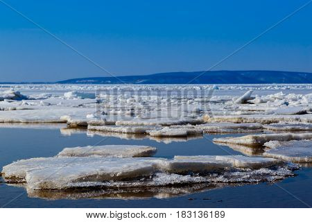 Spring Melting Of Ice On The Volga River Against The Background Of Mountains And Blue Sky