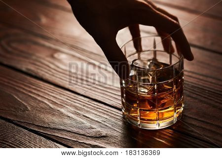 Man's hand holding Glass of whiskey with ice cubes on rustic wooden table with copy-space