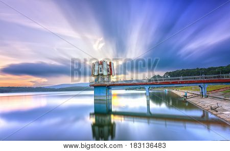 Dalat, Vietnam - March 28th, 2017: Architectural beauty sunset with clouds hydrogen towers leads to center fanciful, smooth water long exposure. This is power supply to entire city of Da Lat, Vietnam