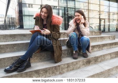 Two happy smiling college girl students on the campus