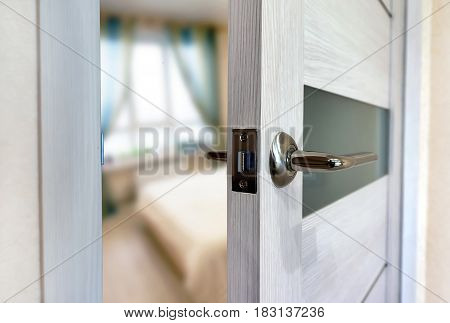 Close-up elements of the interior of the apartment. Ajar white door. Chrome door handle.