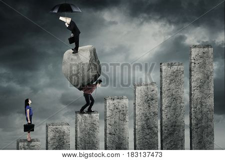 Young businesswoman looking at her partners standing on a big boulder and carrying the boulder on the graph