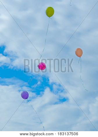 Multicolored Balloons Fly Against The Blue Sky And Clouds