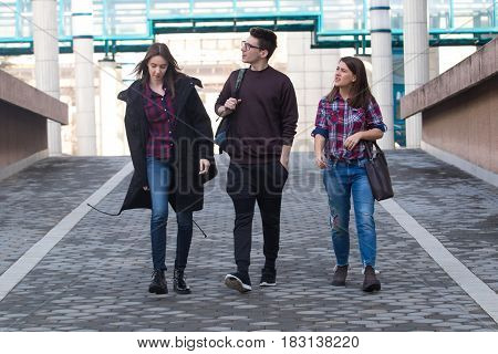 Three young students walking in the campus