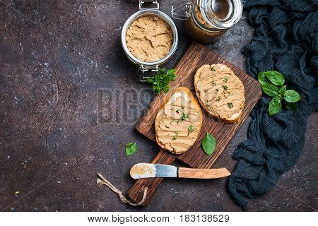 Fresh homemade chicken liver pate on bread over rustic background, top view