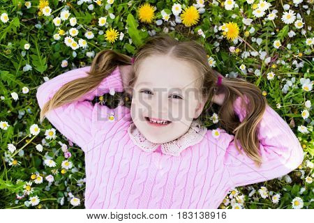 Child on green grass lawn with daisy and dandelion flowers on sunny summer day. Kid playing in garden. Little girl dreaming and relaxing. Kids on Easter egg hunt in spring park. Children gardening.