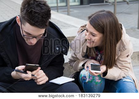 Girl and boy collage students with smart phones and notebook learning
