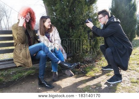 Young photographer take photos of two smiling girl students