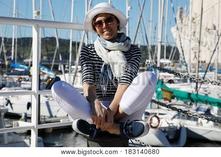 A middle-aged woman in a good mood dressed in a navy style sits in the background of the bay with yachts