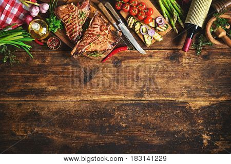 Grilled T-bone steaks with fresh herbs, vegetables and wine bottle on rustic wooden board