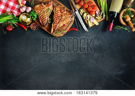 Grilled T-bone steaks with fresh herbs, vegetables and wine bottle