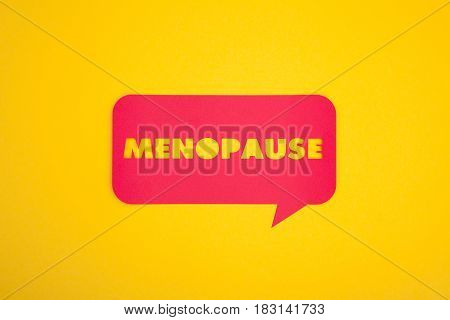 From above menopause word cut-out in a paper comic cloud isolated on yellow.