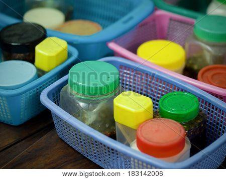 COLOR PHOTO OF SEASONING PLASTIC BOTTLES IN PLASTIC BASKETS