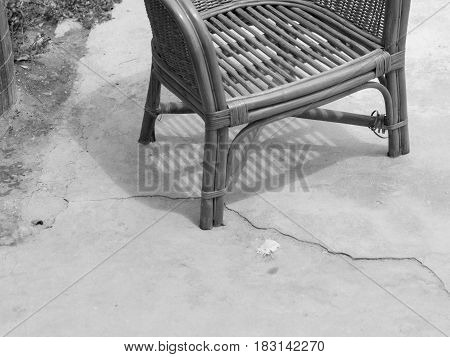 BLACK AND WHITE PHOTO OF RATTAN CHAIR ON CONCRETE GROUND