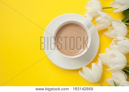 A bunch of flowers placed at the coffee cup isolated on yellow.