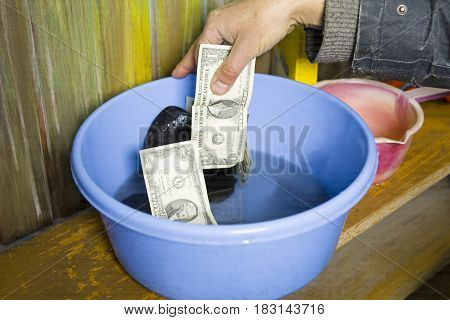 Male hand washing cash and laundry in a blue basin concept of money laundering