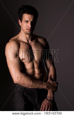 Strong athletic young man. Strong muscular athlete posing on black.